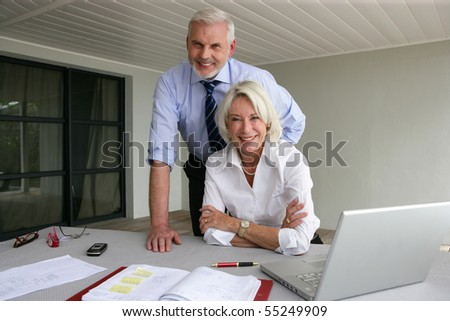 Portrait of a senior couple in suit in front of a laptop computer - stock photo