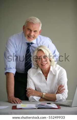 Portrait of a senior couple in suit in front of a laptop computer on gray background - stock photo