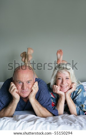 Portrait of a senior couple lying on a bed - stock photo