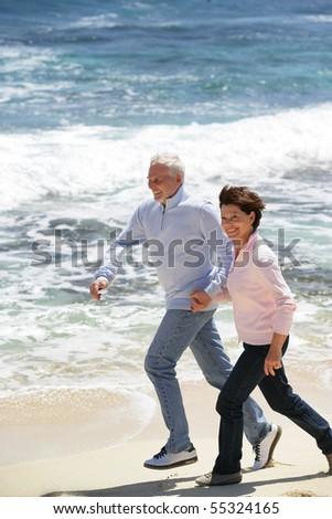 Portrait of a senior couple running on the beach - stock photo