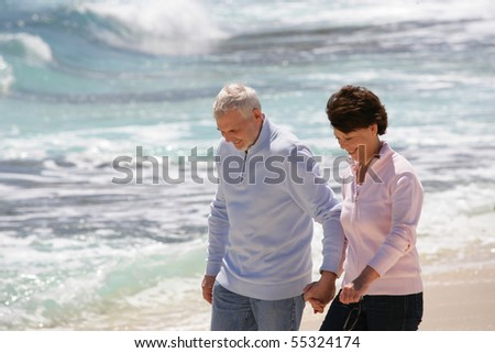Portrait of a senior couple walking by the beach - stock photo