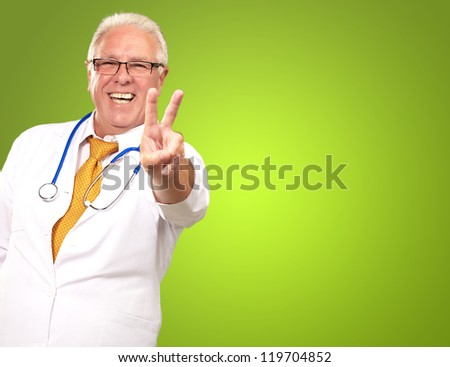 Portrait Of A Senior Doctor On Green Background - stock photo