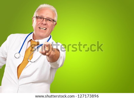 Portrait Of A Senior Doctor Pointing On Green Background - stock photo