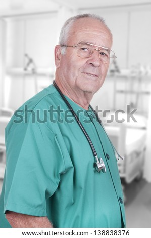 portrait of a senior doctor standing in an hospital ward - stock photo