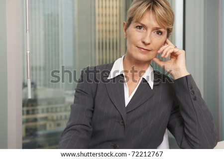 Portrait of a senior executive by a window smiling looking at camera - stock photo
