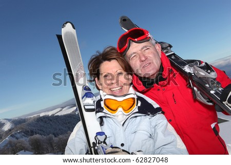 Portrait of a senior man and a senior woman smiling with skis in snow - stock photo