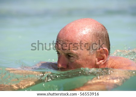 Portrait of a senior man bathing in the sea - stock photo