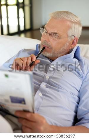 Portrait of a senior man doing crosswords - stock photo