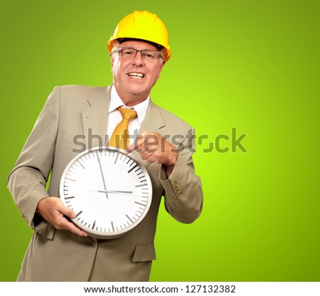 Portrait Of A Senior Man Holding A Wall Watch On Green Background - stock photo