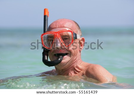 Portrait of a senior man in the sea with a snorkel and goggles