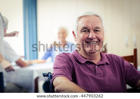 Portrait of a senior man in wheelchair in the retirement house - stock photo