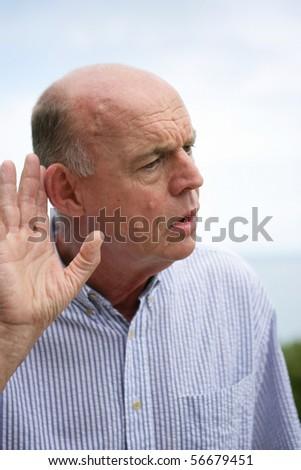 Portrait of a senior man listening carefully - stock photo