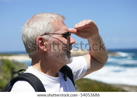 Portrait of a senior man looking away in front of the sea