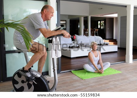 Portrait of a senior man making exercise bike and a senior woman doing yoga - stock photo