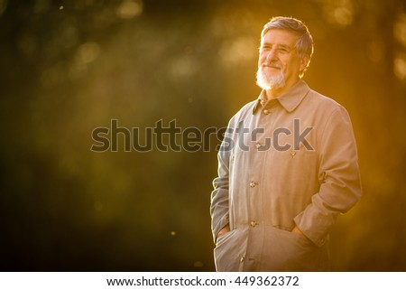 Portrait of a senior man outdoors, walking in a park (shallow DOF; color toned image) - stock photo