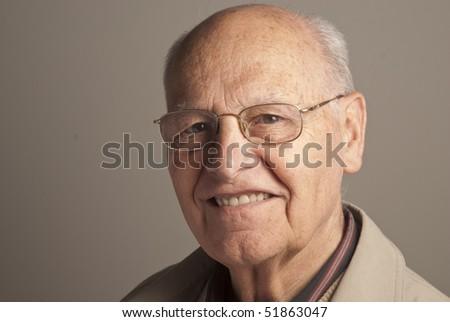 Portrait of a senior man over grey background - stock photo