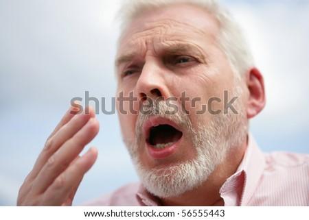 Portrait of a senior man ready to sneeze - stock photo