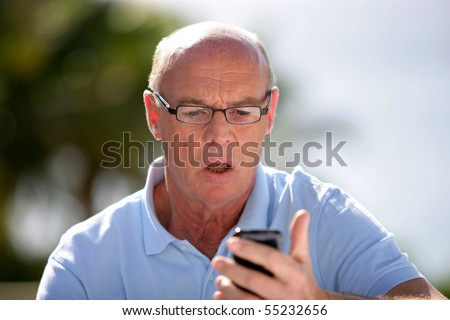 Portrait of a senior man shocked in front of a mobile phone - stock photo