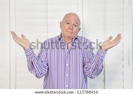 Portrait of a senior man shrugging shoulders in confusion - stock photo