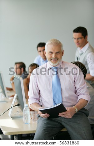 Portrait of a senior man sitting on a desk holding documents - stock photo