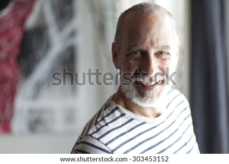 Portrait Of A Senior Man Smiling At The Camera - stock photo