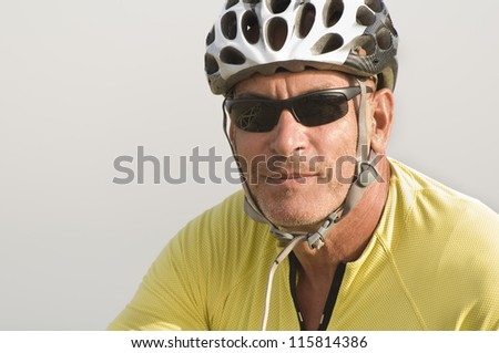 Portrait of a senior man smiling wearing a cycling helmet