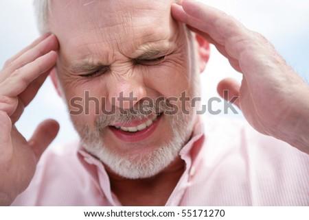Portrait of a senior man suffering from headache - stock photo
