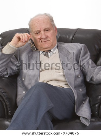 Portrait of a senior man thinking deeply in his office armchair. - stock photo