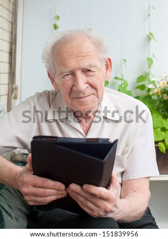 portrait of a senior man with a touchpad PC - stock photo