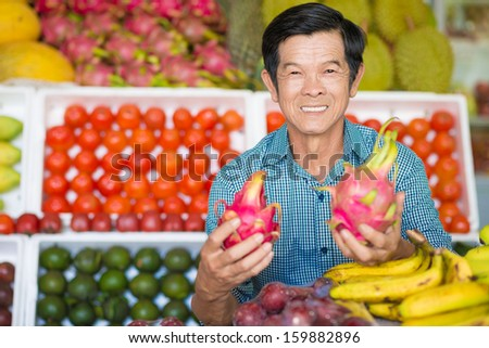 Portrait of a senior man with exotic fruits in hands on the foreground - stock photo
