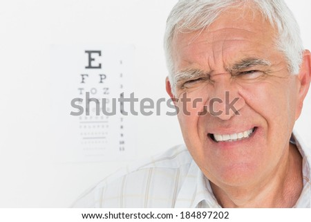 Portrait of a senior man with eye chart in the background at medical office - stock photo