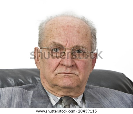 Portrait of a senior man with glasses sitting in an armchair - stock photo