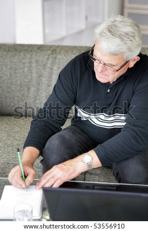 Portrait of a senior man writing on a document - stock photo