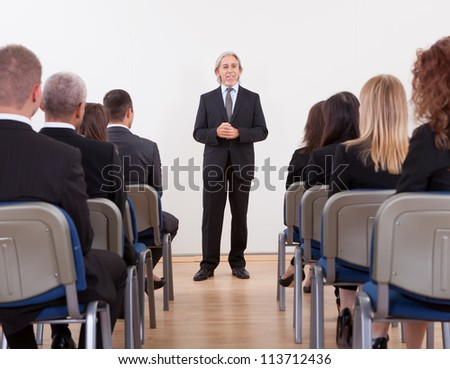 Portrait Of A Senior Manager Giving Presentation To His Colleagues