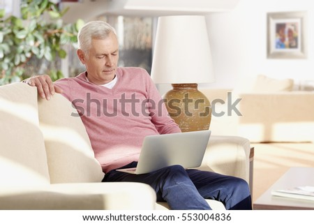 Portrait of a senior retired man using his laptop while working from home.