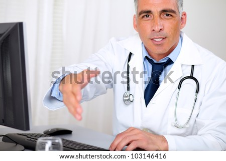 Portrait of a senior trustworthy doctor in from the computer while greeting and looking to you - stock photo