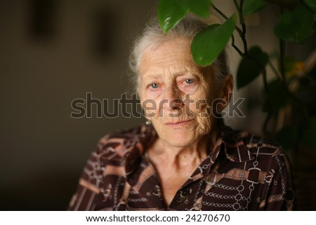 Portrait of a senior woman at home, thinking - stock photo