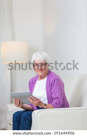 Portrait of a senior woman at home using a tablet computer - Looking happy, looking at the camera, smiling while sitting on the sofa in her living room - stock photo