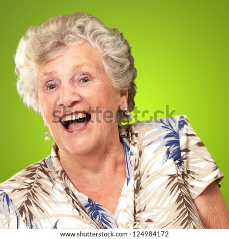 Portrait Of A Senior Woman Happy On Green Background - stock photo