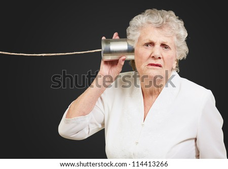 Portrait of a senior woman hearing with metal tin on black background - stock photo