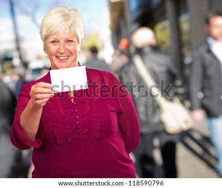 Portrait Of A Senior Woman Holding A Blank Card, Background - stock photo