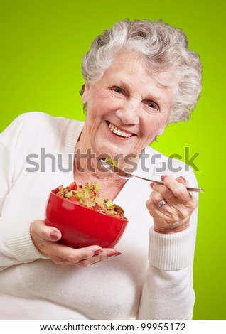 portrait of a senior woman holding a cereal bowl against a green background - stock photo