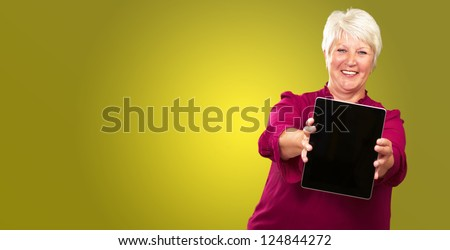 Portrait Of A Senior Woman Holding A Laptop On Green Background - stock photo