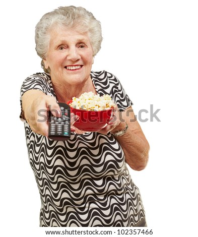 portrait of a senior woman holding a pop corn bowl and changing channel of the tv over a white background