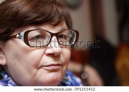 Portrait of a senior woman in glasses - stock photo