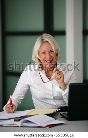 Portrait of a senior woman in suit in front of a laptop computer - stock photo