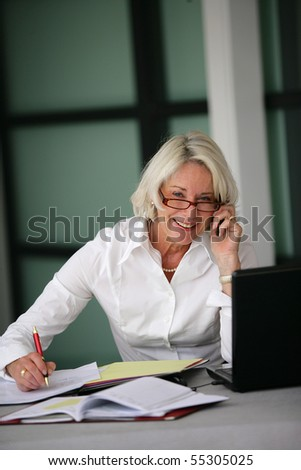 Portrait of a senior woman in suit with a phone and a laptop computer - stock photo