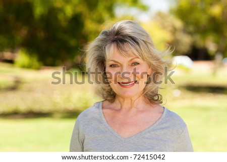 Portrait of a senior woman in the park - stock photo
