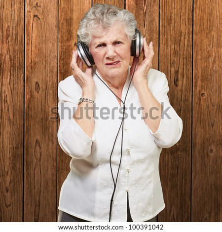 portrait of a senior woman listening to music against a wooden wall - stock photo