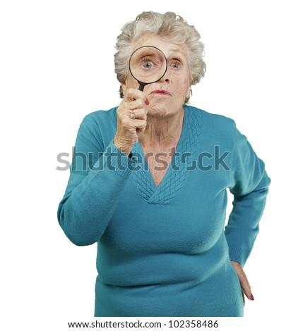 portrait of a senior woman looking through a magnifying glass over a white background